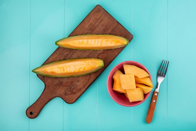 Top view of fresh and delicious cantaloupe melon slices on wooden kitchen board with slices of melon on bowl on blue