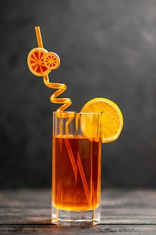 Top view of fresh delicious juice in a glass with orange lime and tube on dark background