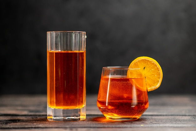 Top view of fresh delicious juice in two glasses with orange lime on dark background