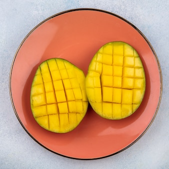 Top view of fresh and delicious sliced mangos onn orange plate on white