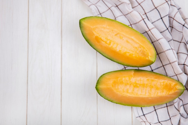 Top view of fresh and delicious slices of cantaloupe melon on checked tablecloth on white wood with copy space