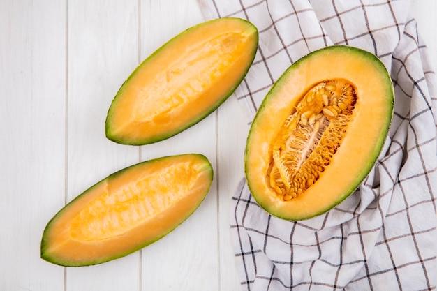 Vista dall'alto di fette fresche e deliziose di melone cantalupo con semi sulla tovaglia a quadri su legno bianco
