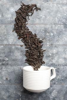 灰色の素朴な机の上のカップの内側と外側の新鮮な乾燥茶の上面図