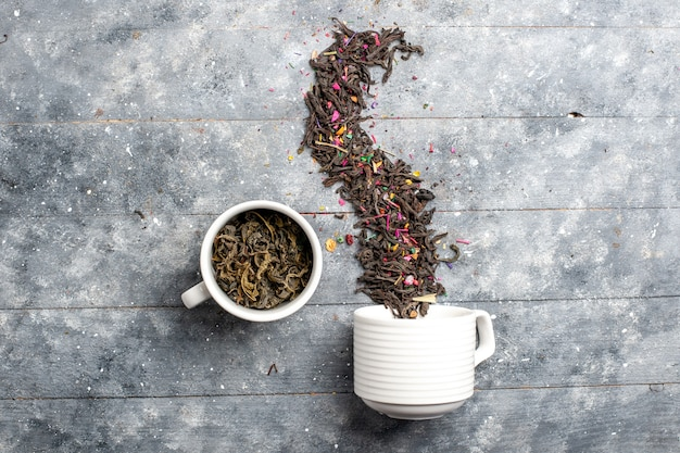 Вид сверху свежего сушеного чая внутри и снаружи чашки на сером деревенском пространстве