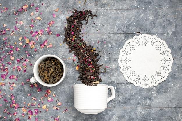 Vista dall'alto tè essiccato fresco all'interno e all'esterno della tazza sulla scrivania rustica grigia