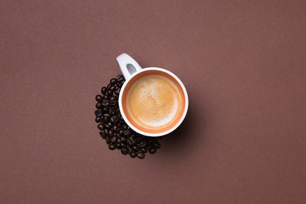 Top view of a fresh espresso cup surrounded by coffee beans on brown surface