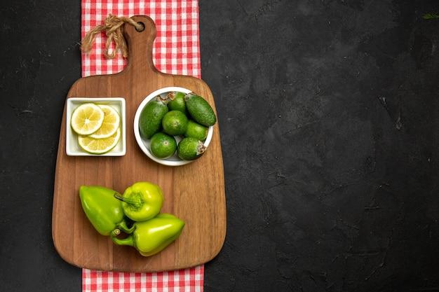 Vista dall'alto feijoa fresca con peperone verde e limone sulla superficie scura della farina di agrumi di frutta