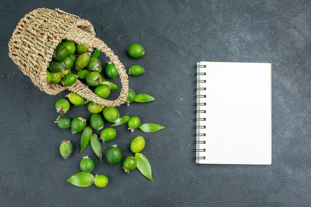 Top view fresh feijoas in basket a notebook on dark surface