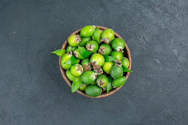 Top view fresh feijoas in bucket dark surface with copy space