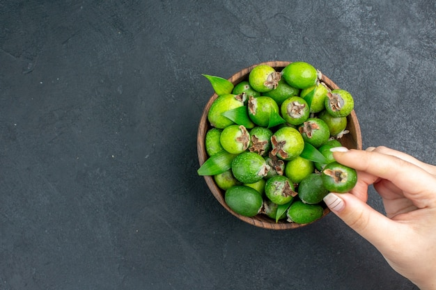 Top view fresh feijoas in bucket female hand holding feijoa on dark surface with copy space