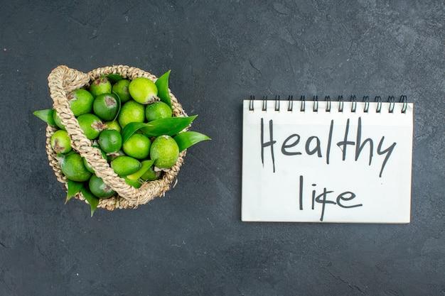 Вид сверху свежие фейхоа в корзине здорового образа жизни, написанные на ноутбуке на темной поверхности