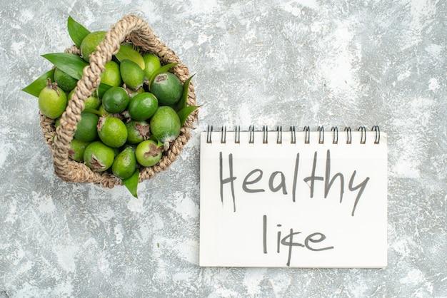 Вид сверху свежие фейхоа в плетеной корзине здорового образа жизни, написанные на ноутбуке на серой изолированной поверхности