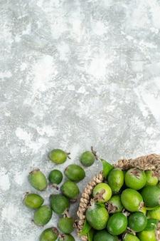 복사 공간 회색 절연 표면에 고리 버들 바구니에 상위 뷰 신선한 feijoas