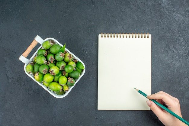 Top view fresh feijoas on plastic basket green pwncil in female hand notepad on dark surface