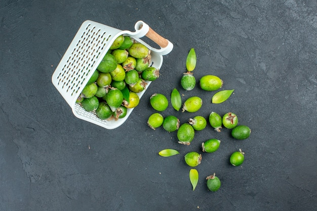 Top view fresh feijoas scattered from plastic basket on dark surface with copy place
