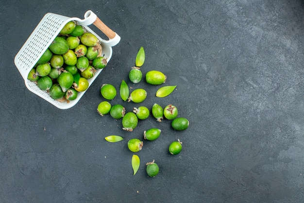 Top view fresh feijoas scattered from plastic basket on dark surface with copy space