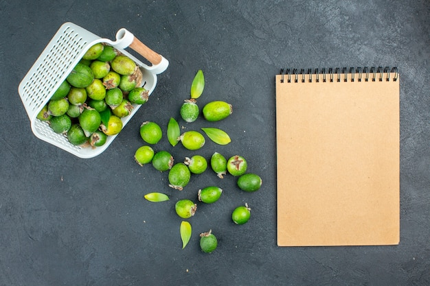 Top view fresh feijoas scattered from plastic basket notebook on dark surface