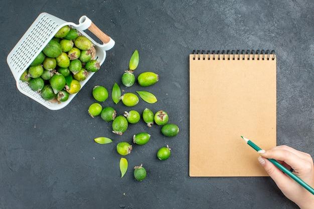 Вид сверху свежие фейхоа, разбросанные из пластиковой корзины, карандаш для ноутбука в женской руке на темной поверхности