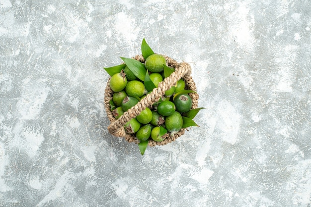 Top view fresh feijoas in wicker basket on grey isolated surface free space