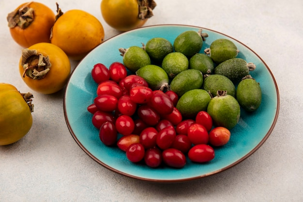 Top view of fresh feijoas with cornelian cherries on a blue dish with persimmons isolated on a grey background