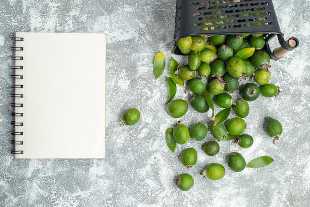 Вид сверху свежих фейхоа, разбросанных из записной книжки корзины на серой поверхности