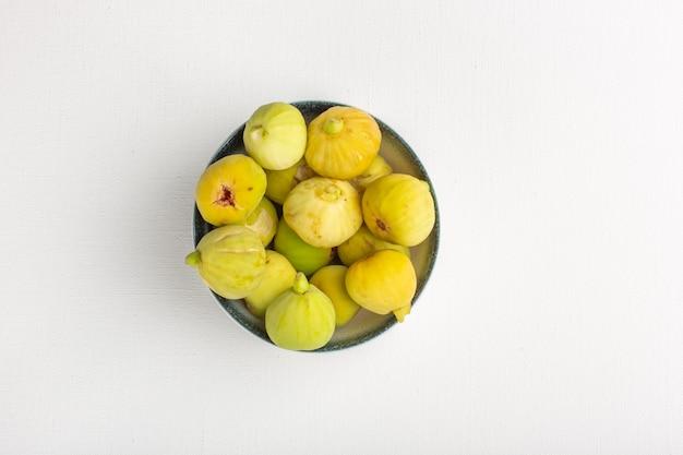 Вид сверху свежего инжира, сладких и вкусных плодов внутри тарелки на белой поверхности