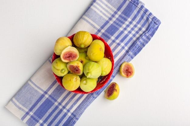 Вид сверху свежего инжира, сладких вкусных плодов внутри красной тарелки на белом столе