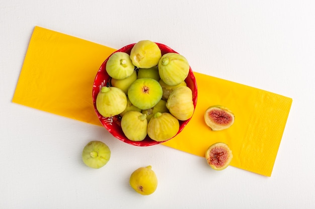 Top view fresh figs sweet and delicious fetuses inside red plate on the white surface
