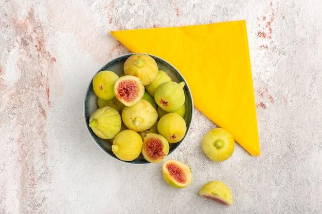 Вид сверху свежего инжира, сладких плодов внутри тарелки на светлой белой поверхности