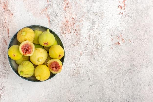 Vista dall'alto fichi freschi feti dolci all'interno del piatto sulla superficie bianca