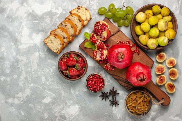 白い机の上にザクロのケーキとブドウと新鮮なイチジクの上面図