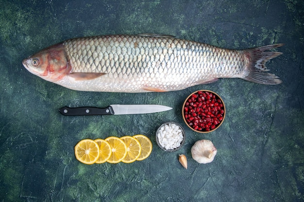 Вид сверху свежая рыба, дольки лимона, нож, миска с семенами граната на кухонном столе