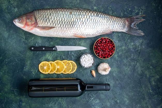 Vista dall'alto pesce fresco fette di limone coltello semi di melograno ciotola bottiglia di vino sul tavolo della cucina