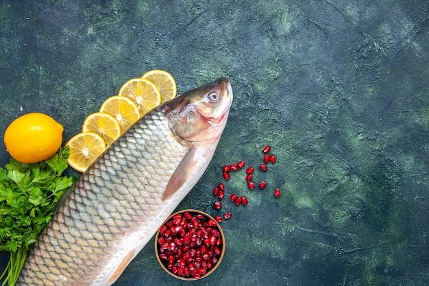 Вид сверху свежая рыба, дольки лимона, миска с семенами граната на столе, свободное место