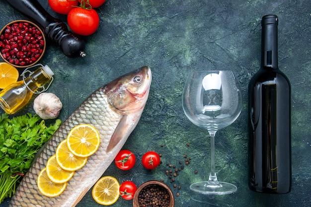 Вид сверху свежая рыба, дольки лимона, миска с семенами граната, бутылка вина и стакан на столе, свободное место