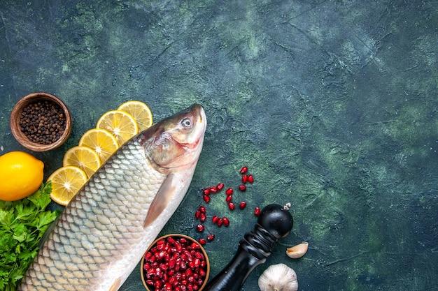 Вид сверху свежей рыбы, мельница для перца, дольки лимона, миска с семенами граната на столе со свободным пространством