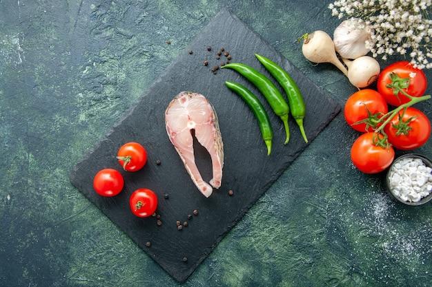 暗い背景にトマトとピーマンを添えた新鮮な魚のスライスの上面図シーフード海の肉海の食事水唐辛子料理