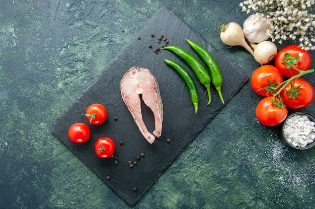 Top view fresh fish slice with tomatoes and green pepper on dark background seafood ocean meat sea meal water pepper dish food
