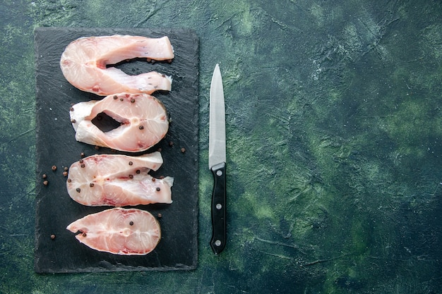 Vista dall'alto di fette di pesce fresco su sfondo scuro carne dell'oceano piatto di frutti di mare farina di mare cibo pepe spazio libero