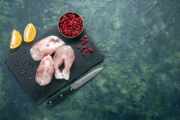 Top view fresh fish slices on dark background ocean meat seafood sea meal dish food pepper water raw
