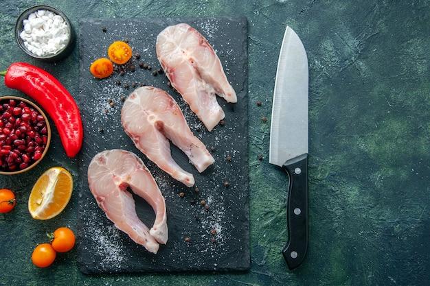 Vista dall'alto di fette di pesce fresco su sfondo scuro frutti di mare oceano carne pasto piatto insalata acqua pepe cibo
