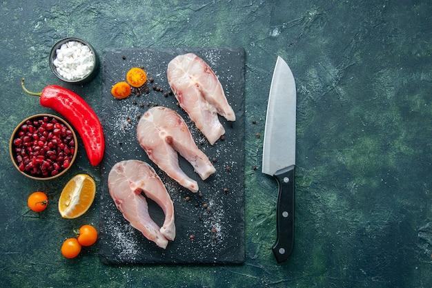 Vista dall'alto di fette di pesce fresco sullo sfondo scuro frutti di mare oceano carne piatto di farina di mare insalata acqua pepe cibo
