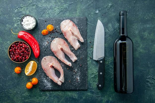 Vista dall'alto fette di pesce fresco sulla superficie scura frutti di mare oceano carne piatto di mare insalata acqua pepe cibo