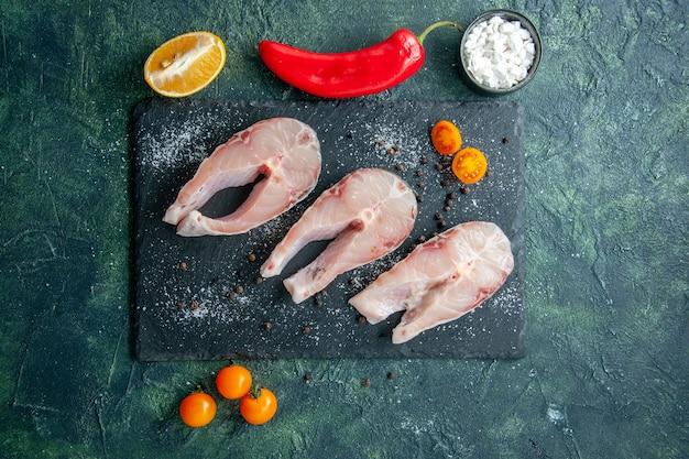 Vista dall'alto fette di pesce fresco sul tavolo scuro frutti di mare oceano carne piatto di farina di mare insalata acqua pepe cibo