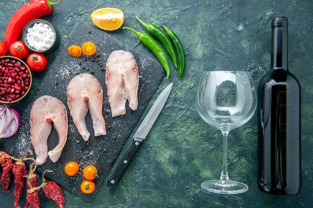 暗い背景の皿サラダシーフード海肉海ワインコショウ食品水ミールの上面図新鮮な魚のスライス