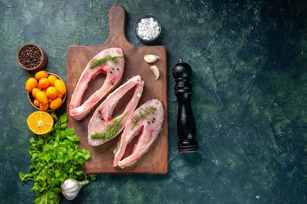 Vista dall'alto fette di pesce fresco con verdure e kumquat su sfondo scuro