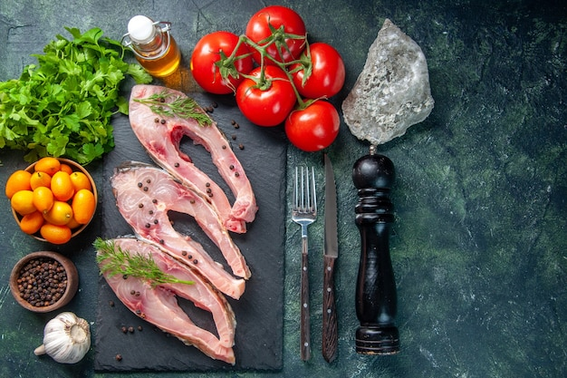 Top view fresh fish slices with kumquats on dark blue background
