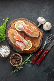 Fette di pesce fresco vista dall'alto con limone e aglio sul tavolo scuro