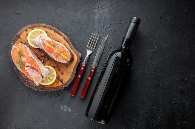 暗いテーブルの上のレモンスライスとカトラリーと新鮮な魚のスライスの上面図
