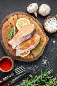 어두운 탁자에 레몬 조각과 조미료를 넣은 신선한 생선 조각
